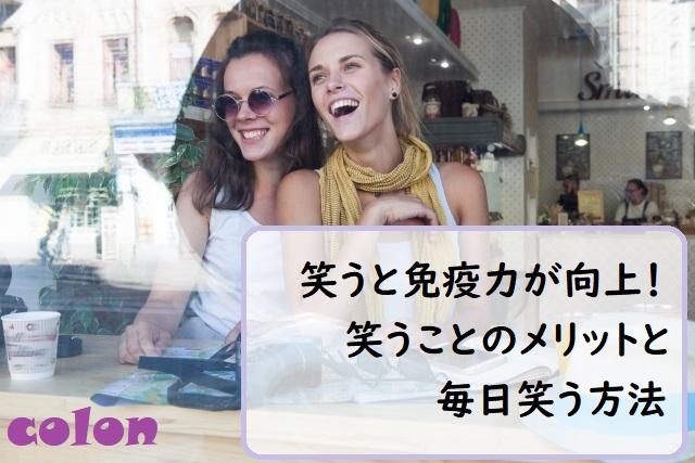 カフェの窓際で笑う外国人女性2人